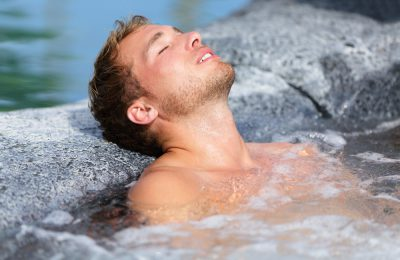 A photograph of a man in a rock pool relaxing