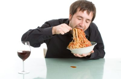 A photograph of a man eating pasta with a glass of red wine