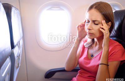 A woman struggling with a headache on an aeroplane