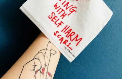 A photograph of a womans arm and hand with a paper notice about self harm