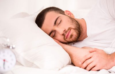 A photograph of a man sleeping on a completely white bed